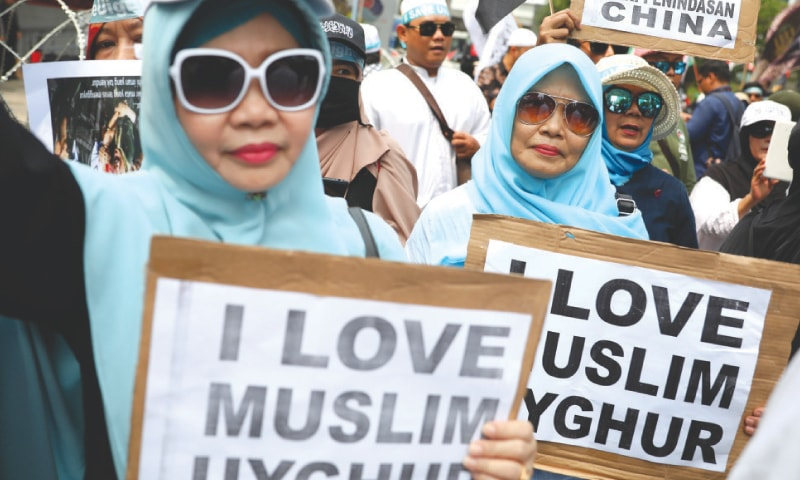 Jakarta: Women hold posters during a rally outside the Chinese embassy on Friday.—AP