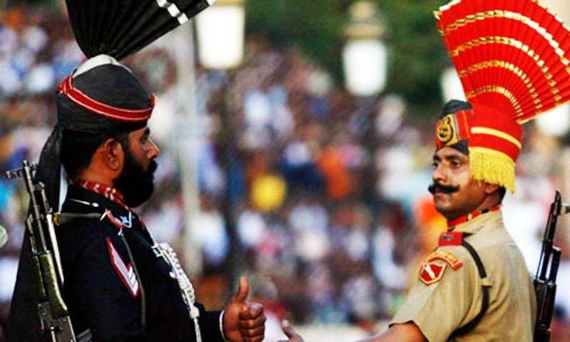 A Pakistani Ranger and an Indian Border Security Force soldier gesture to each other during the daily parade at the Pakistan-India joint check-post at Wagah border. — Reuters
