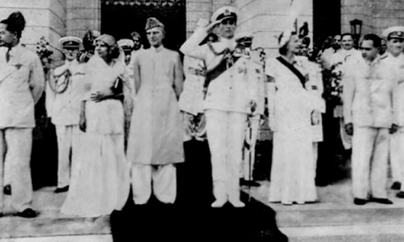 Lord Mountbatten takes the salute on the steps of the Constituent Assembly Hall. Lady Mountbatten is standing next to him and Miss Jinnah is standing next to Mr. Jinnah.