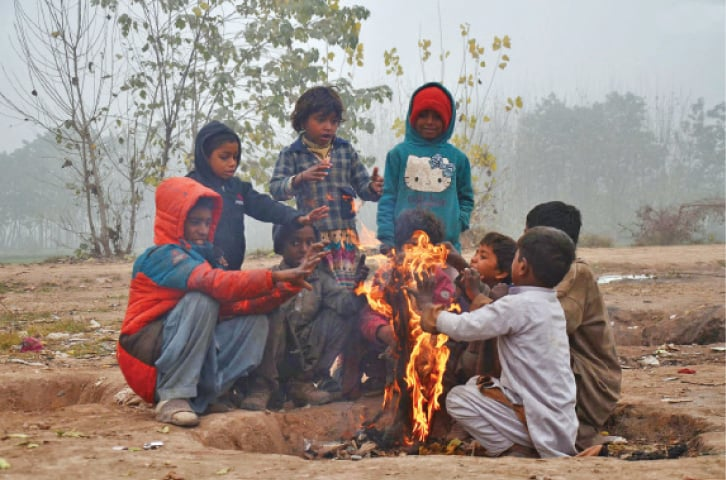 Street children make a fire to warm themselves on a cold and foggy day in Peshawar. — INP