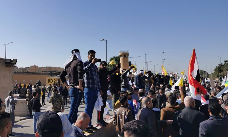Protesters and militia fighters gather to condemn air strikes on bases belonging to  Hashed al-Shaabi (paramilitary forces), outside the main gate of the US Embassy in Baghdad, Iraq on December 31. — Reuters