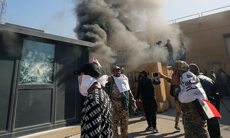 Members of the Iraqi pro-Iranian Hashed al-Shaabi group and protesters set ablaze a sentry box in front of the US embassy building in Baghdad. — AFP