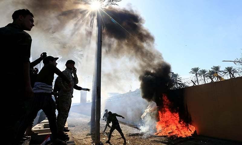 عراقی مظاہرین نے امریکی سفارتخانے کی دیوار کے ساتھ مظاہرین نے آگ لگائی ہوئی ہے— فوٹو: رائٹرز