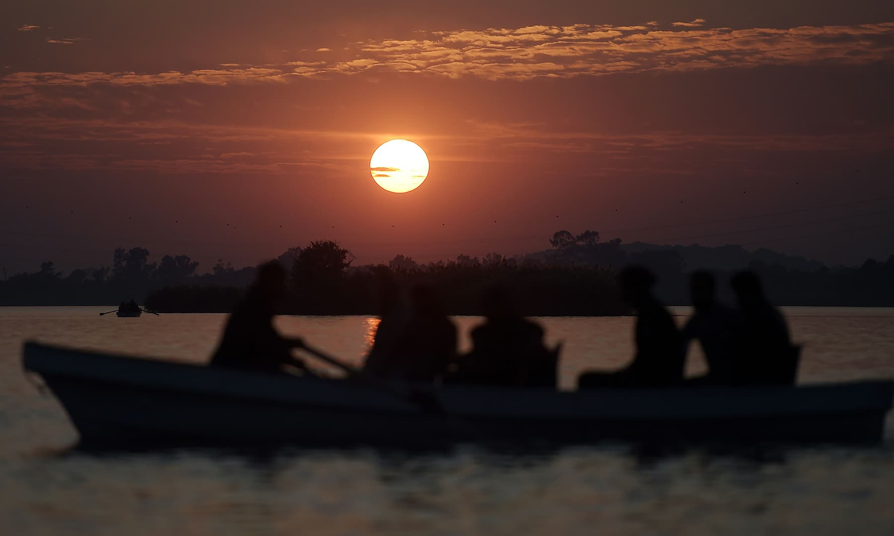 A boatman gives a ride to tourists during the last sunset of 2019 at Lake View Point, in Islamabad on Tuesday. — AFP