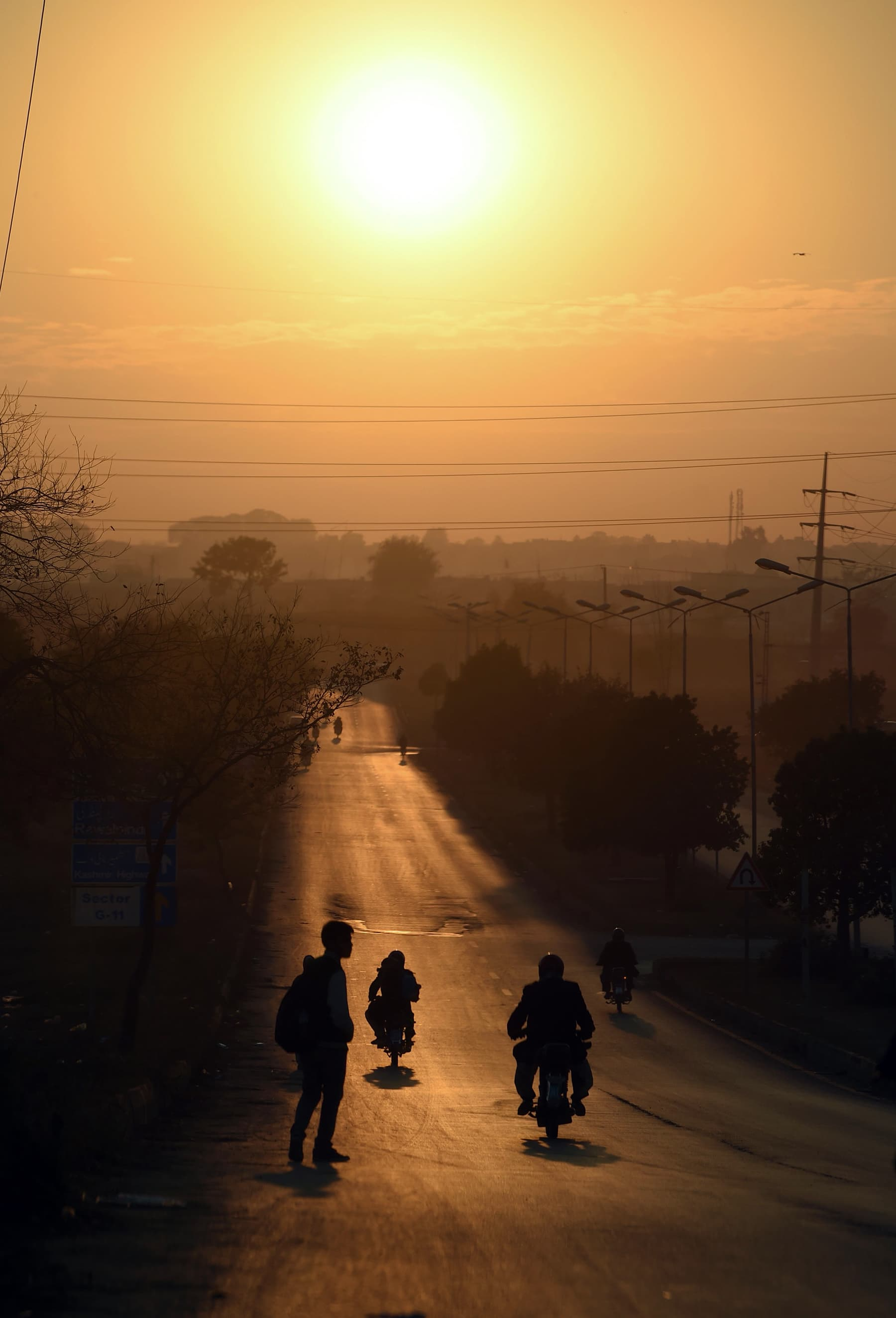 Commuters ride along a road during the last sunset 2019, in Islamabad on Tuesday. — AFP