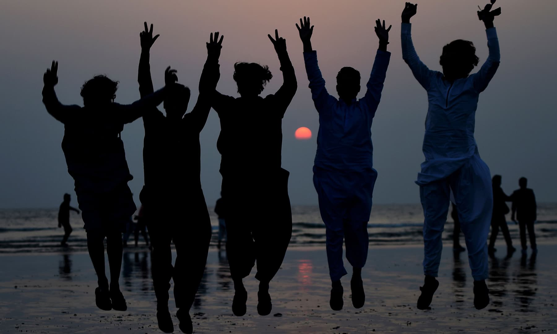 Youths jump for a picture during the last sunset of 2019, in Karachi on Tuesday. — AFP