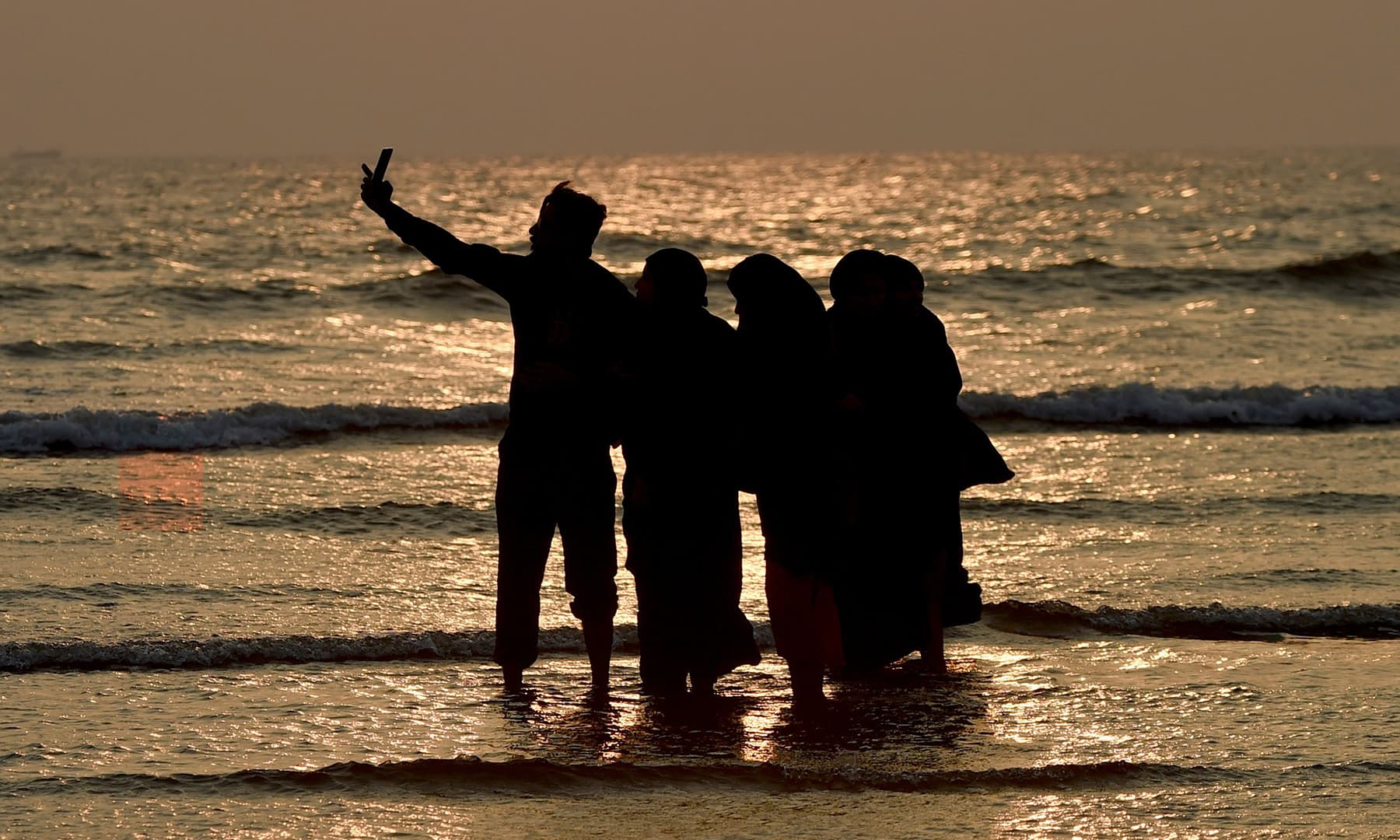 A family takes selfie on a beach during the last sunset of 2019, in Karachi on Tuesday.  — AFP
