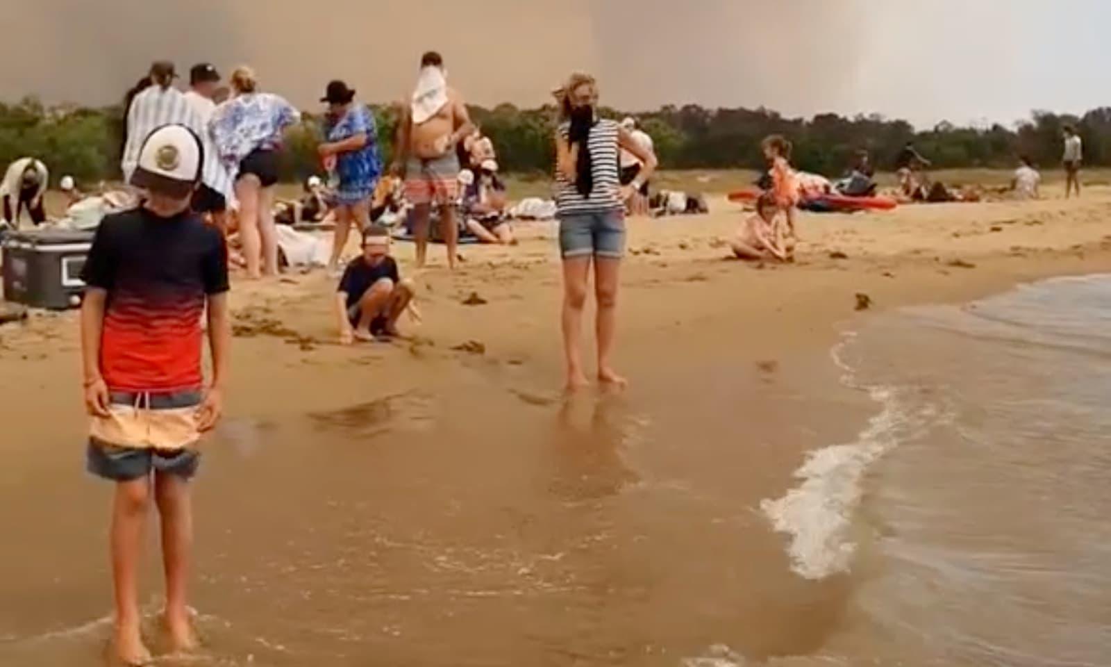 جان بچانے کیلئے سیاح اور مقامی افراد ساحل پر موجود ہیں —فوٹو:رائٹرز