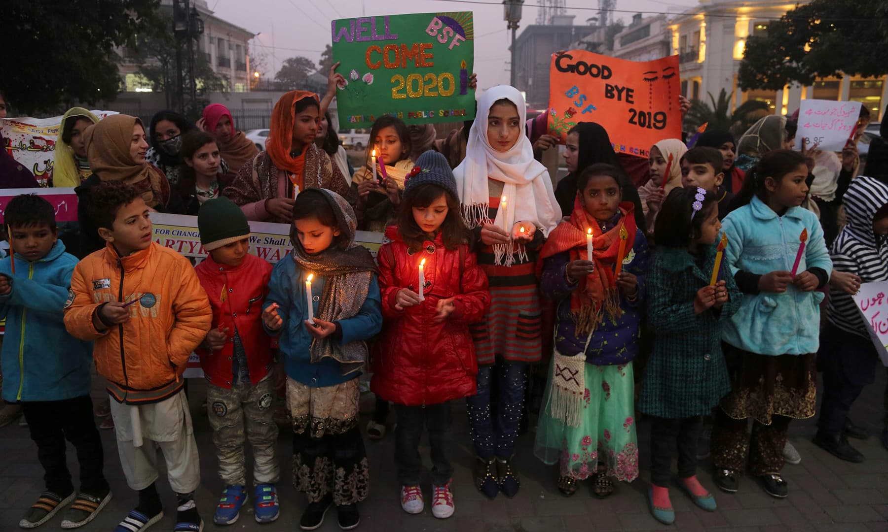Children light candle to welcome the New Year in Lahore on Tuesday. — AFP
