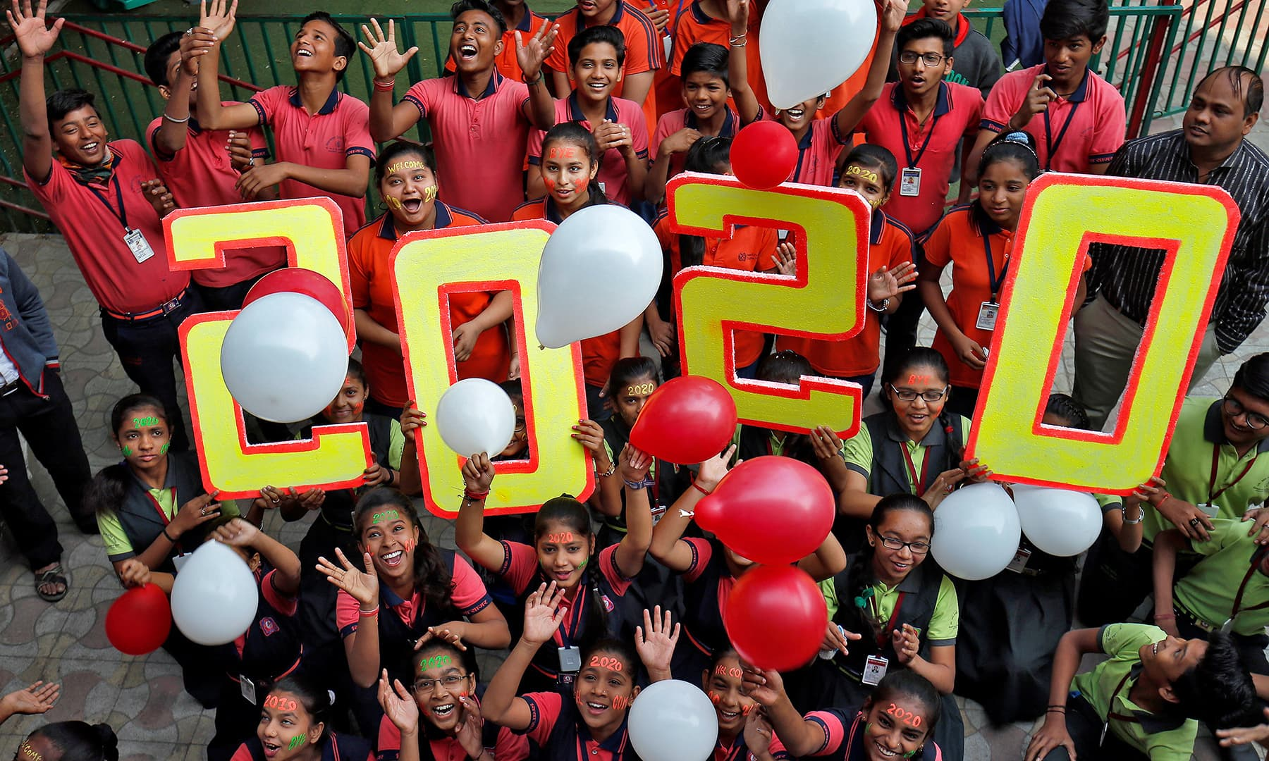 Students cheer as they release balloons during celebrations to welcome the New Year at a school in Ahmedabad, India, on Tuesday. — Reuters
