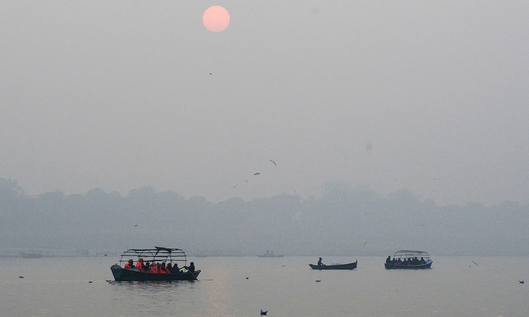 People take an evening boat ride during the last sunset of the year at the Sangam area, the confluence of the rivers Ganges, Yamuna and mythical Saraswati in Allahabad on Tuesday. — AFP
