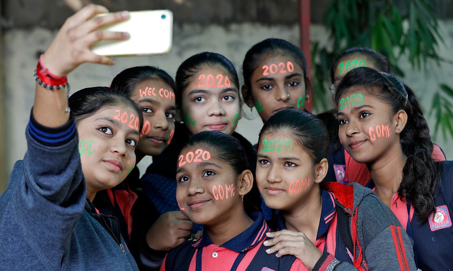 Girls with their faces painted in the digits of number 2020, pose for a selfie during celebrations to welcome the New Year at a school in Ahmedabad, India, on Tuesday. — Reuters