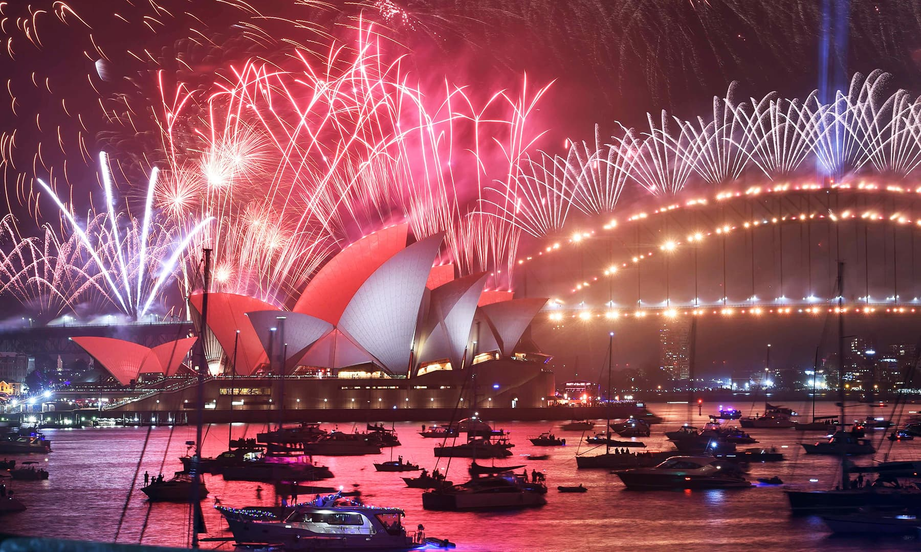 New Year's Eve fireworks erupt over Sydney's iconic Harbour Bridge and Opera House (L) during the fireworks show on January 1, 2020. — AFP