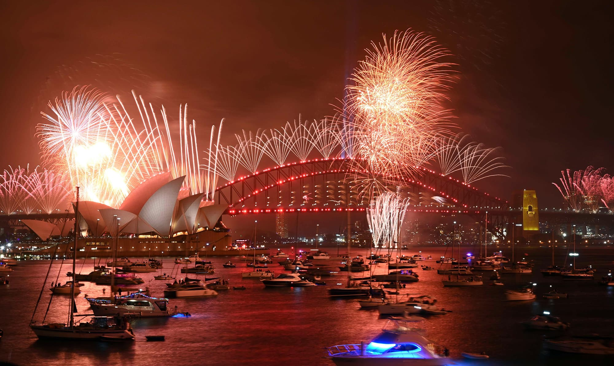 New Year's Eve fireworks erupt over Sydney's iconic Harbour Bridge and Opera House (L) during the fireworks show on January 1, 2020. (Photo by PETER PARKS / AFP) — AFP or licensors