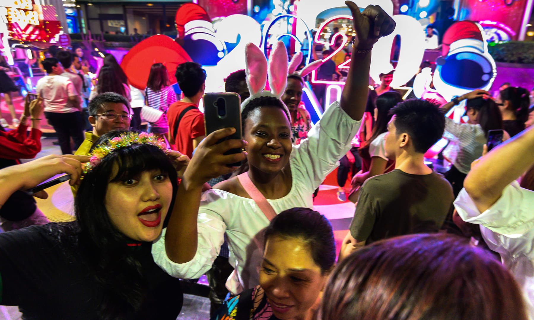 Revellers take a selfie while arriving for a New Year countdown party outside a shopping mall in downtown Bangkok on December 31, 2019. — AFP