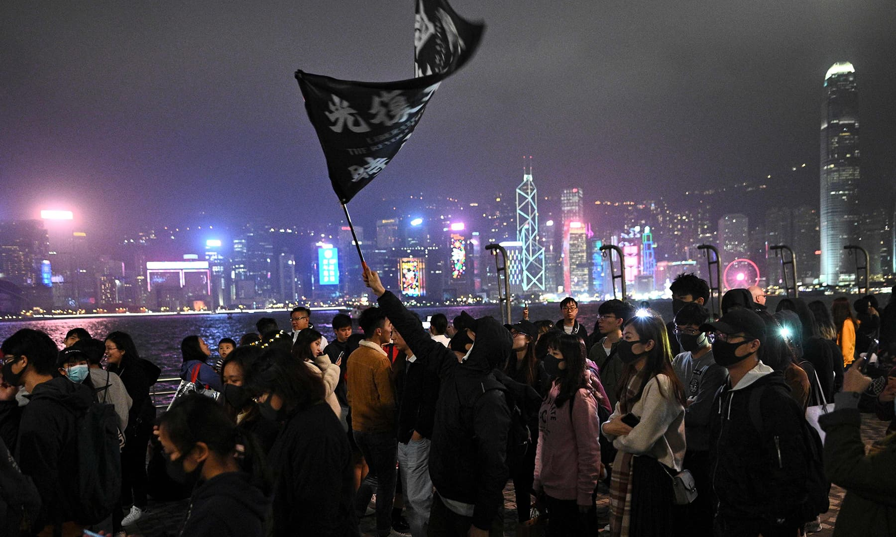 Pro-democracy protesters take part in a march along the promenade of Tsim Sha Tsui district in Hong Kong on Tuesday. — AFP
