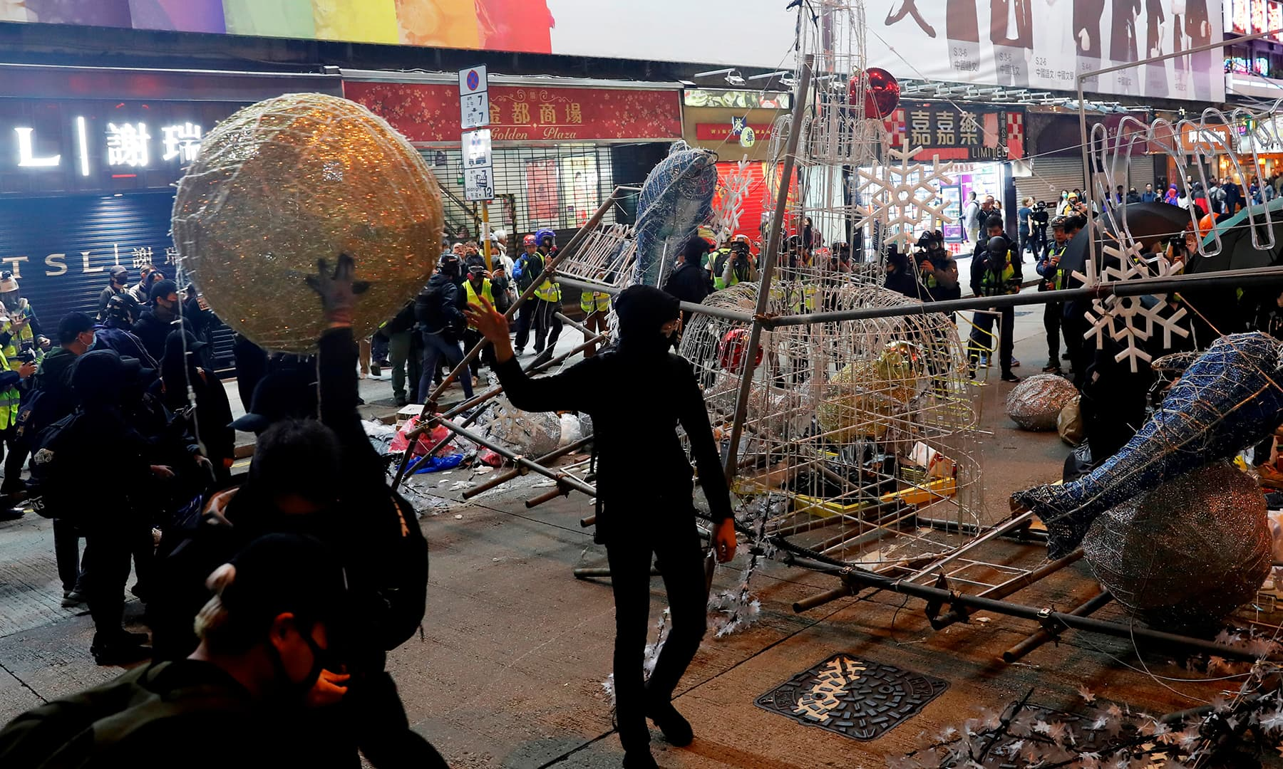 Anti-government protesters tear down Christmas and New Year's decorations during a demonstration on New Year's Eve outside Mong Kok police station in Hong Kong, China, on Tuesday. — Reuters