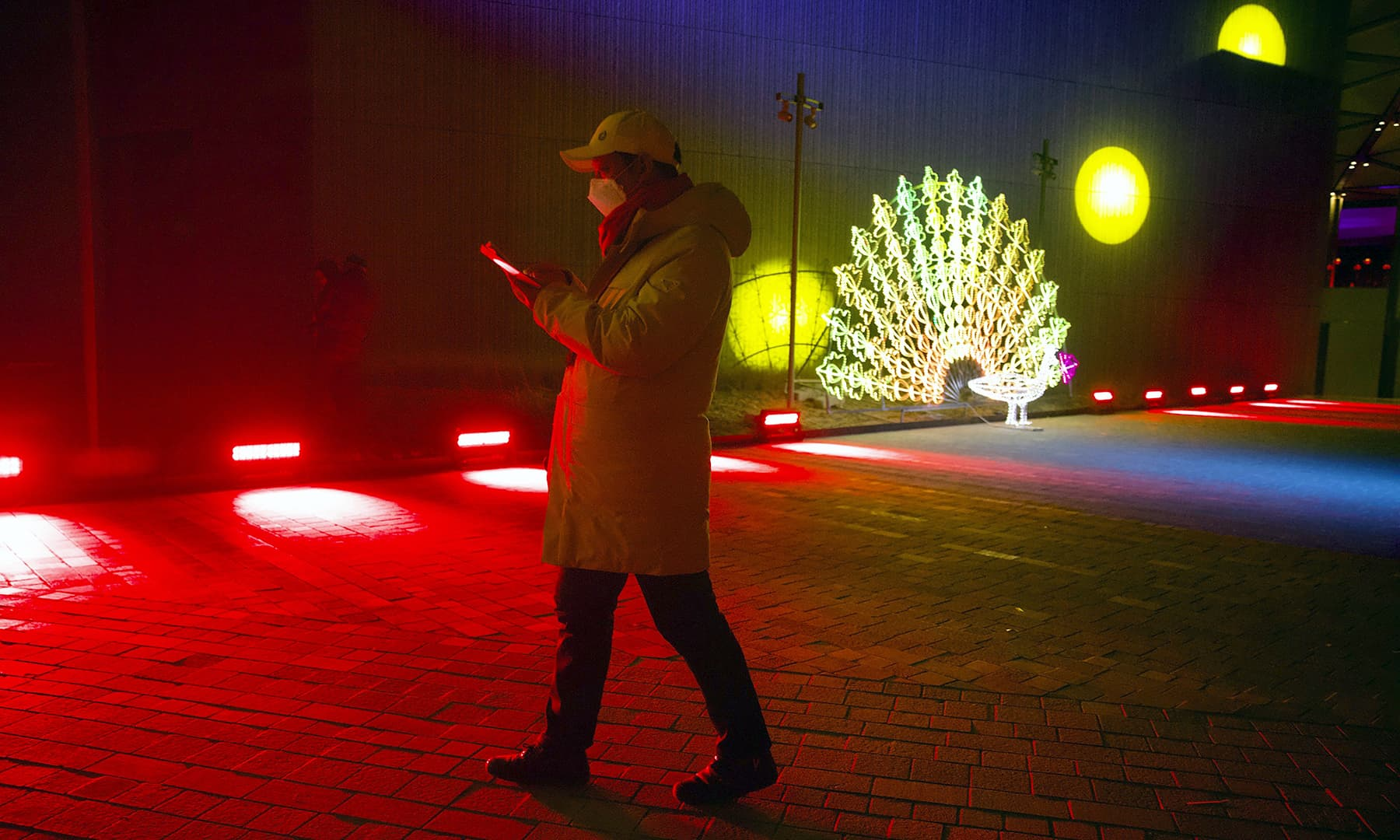 A man walks near a light sculpture before a New Year's Eve countdown event at the 2022 Beijing Winter Olympic headquarters in Bejiing, on Tuesday. — AP