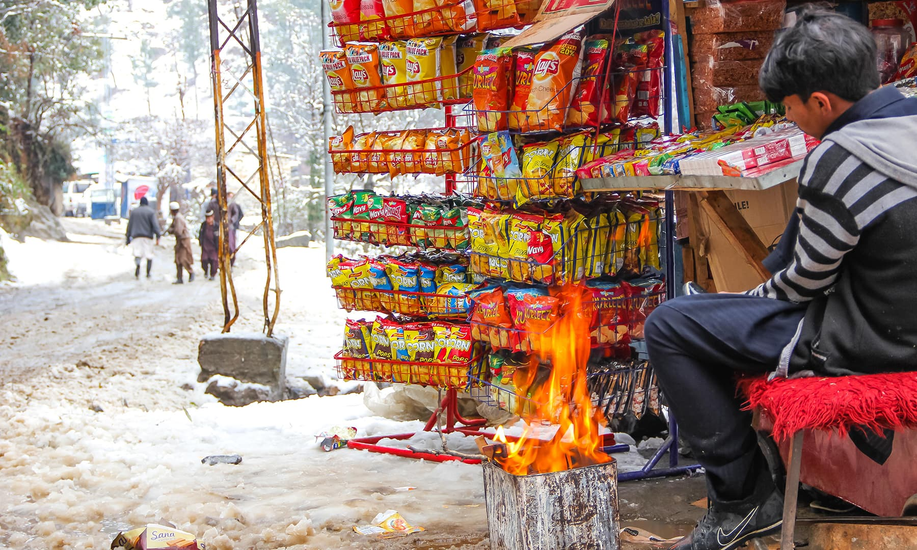 **A sleeping boy keeps himself warm by the fire while selling snacks in Marghuzar valley. — Photo by author**