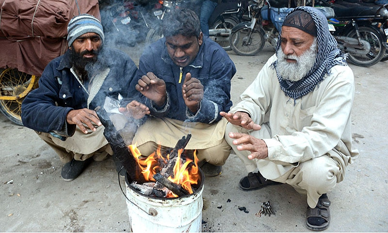 Citizens warm their hands around a makeshift fire in Karachi. — APP