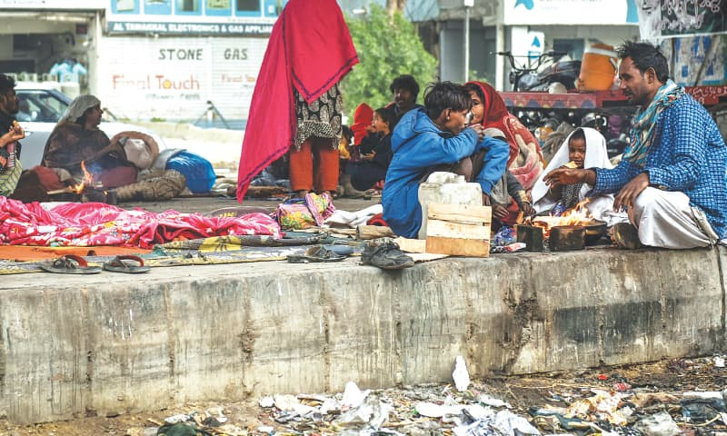 Extremely harsh cold weather with mercury levels dropping to record lows couldn't even improve during the day as many people, like these homeless persons under the Ayesha Manzil flyover, were seen lighting campfires to keep themselves warm, as is usually seen at such places in the evenings, while they had their tea and bread. — Fahim Siddiqi / White Star