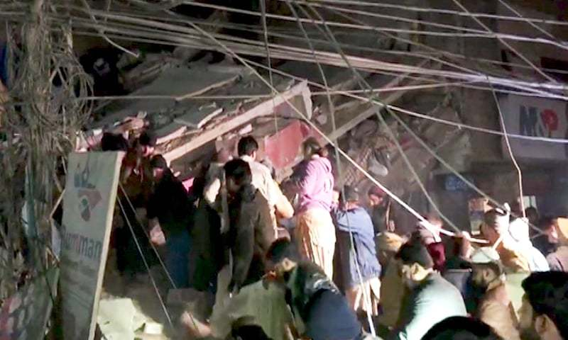People are seen at the site of the building collapse in Sukkur. — DawnNewsTV