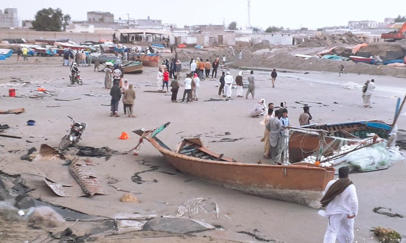 GWADAR: Fishermen look at boats destroyed by sea waves on Thursday.—Dawn