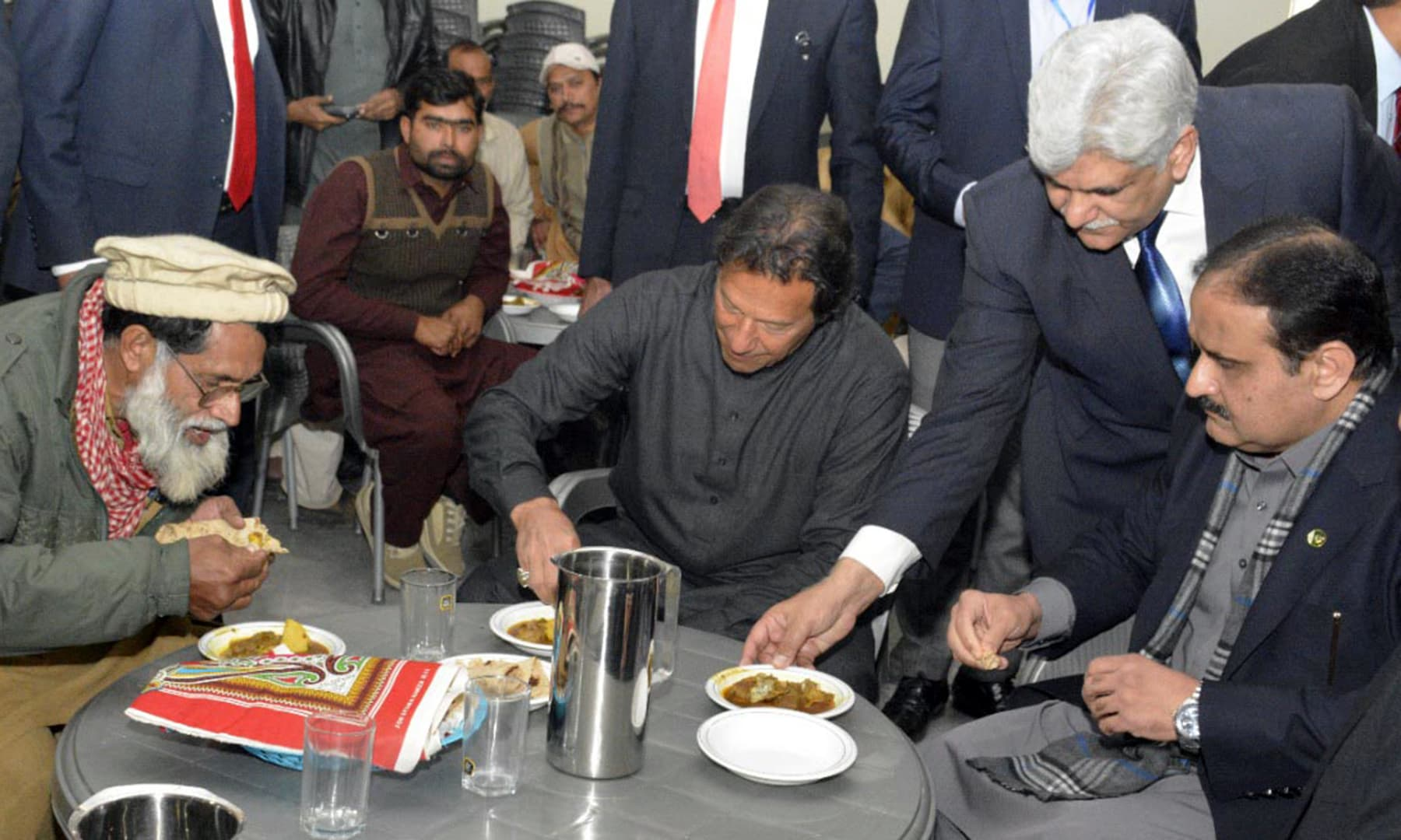 Prime Minister Imran Khan joins people staying at Panahgah for lunch in Faisalabad on Friday. — PID