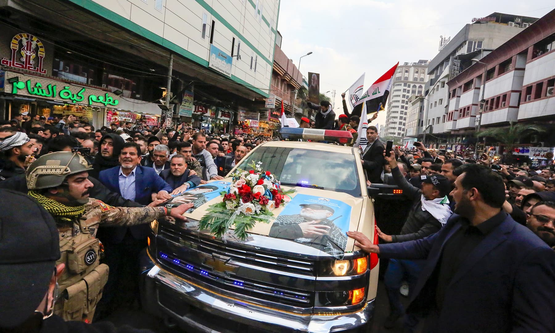 Mourners surround a car carrying the coffin of Iranian military commander Qasem Soleimani, killed alongside Iraqi paramilitary chief Abu Mahdi al-Muhandis in a US air strike, during a funeral procession in Kadhimiya, on January 4. — AFP