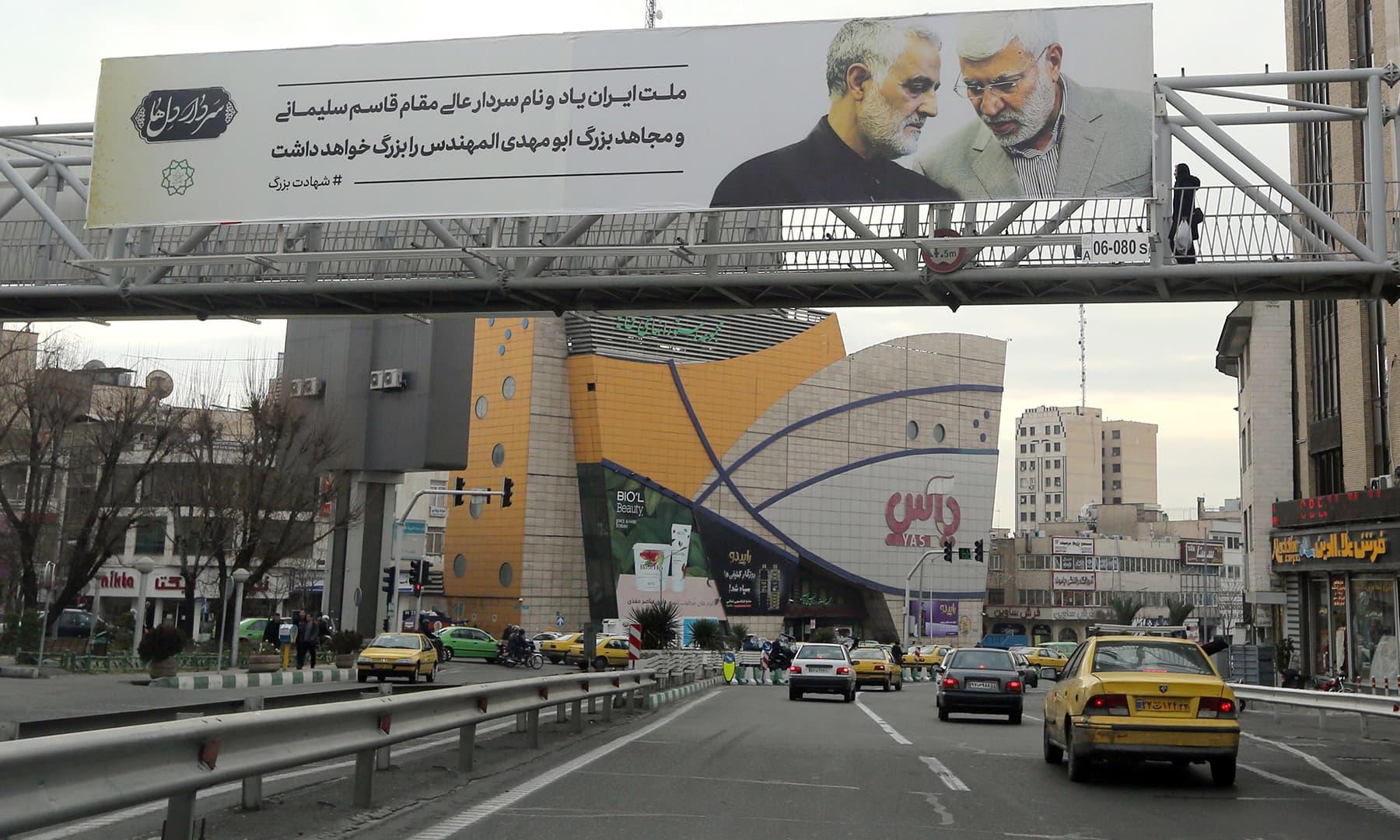 A billboard bearing a portrait of slain Iranian military commander Qasem Soleimani (L) and Iraqi paramilitary chief Abu Mahdi al-Muhandis hangs on a main road in the Iranian capital Tehran on Saturday. — AFP
