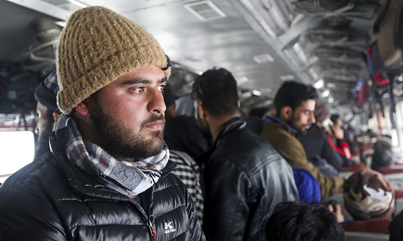 In this picture taken on December 21, 2019, student Bhat Musaddiq Reyaz (L) stands in a crowded carriage of a passenger train on his way back to occupied Kashmir from Banihal. — AFP