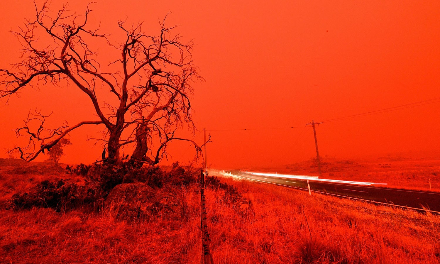 A long exposure picture shows a car commuting on a road as the sky turns red from smoke of the Snowy Valley bushfire on the outskirts of Cooma. — AFP