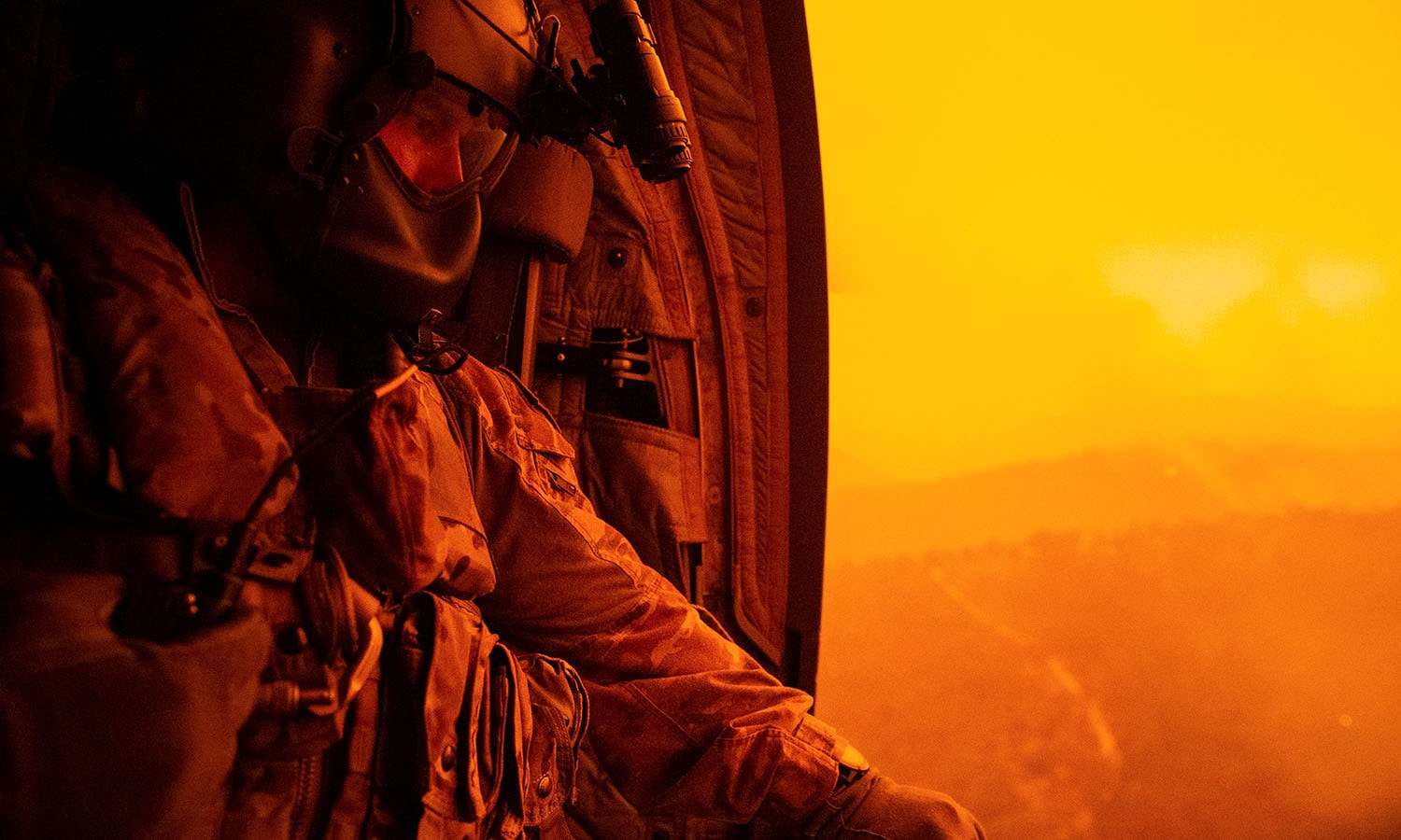 A warrant officer searches the ground from an army helicopter during a flight to Omeo to evacuate local civilian residents during Operation Bushfire Assist. — AFP