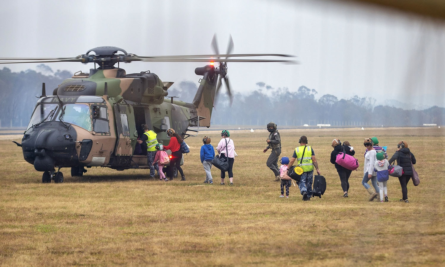 People rush to board a helicopter as the fire ravaged community of Mallacoota is evacuated. — AP