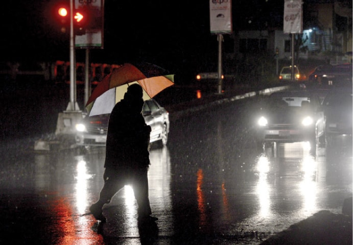 A man holding an umbrella crosses School Road in F-7 in the rain on Monday. — Photo by Mohammad Asim