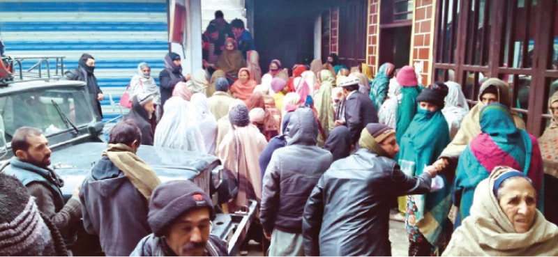 Women wait for their turn outside a mobile franchise in Upper Chitral to get BISP assistance. — Dawn