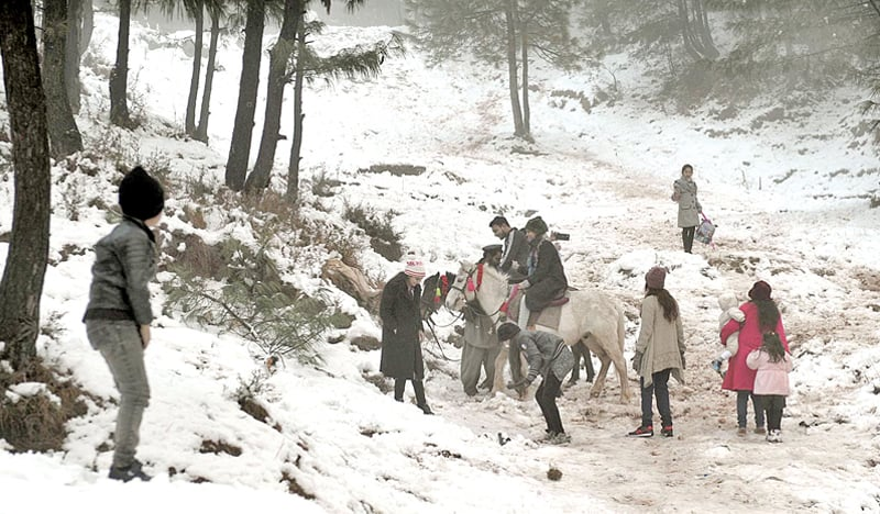 A FAMILY enjoys the snow in Murree on Tuesday. Following the extension of winter vacations in schools in Punjab, many families are visiting the hill station to enjoy the snowfall.—APP