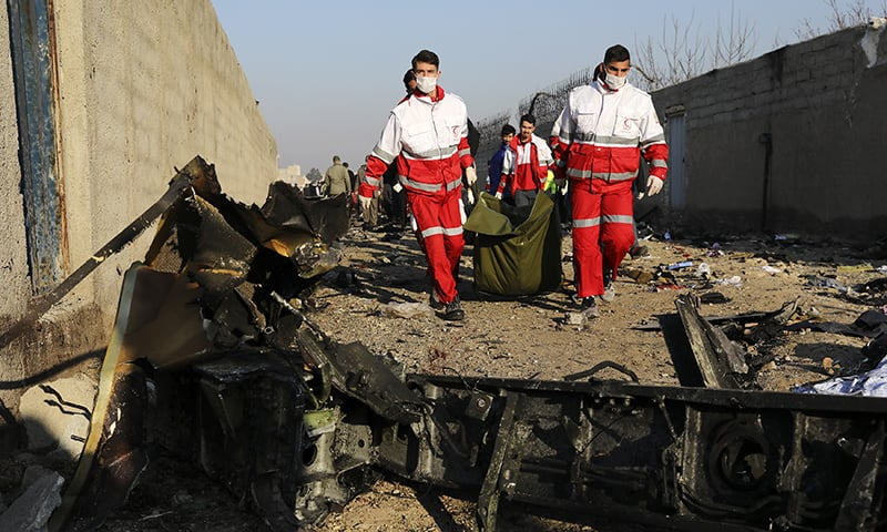 Rescue workers carry the body of a victim of an Ukrainian plane crash among debris of the plane in Shahedshahr, southwest of the capital Tehran, Iran, on Wednesday. — AP