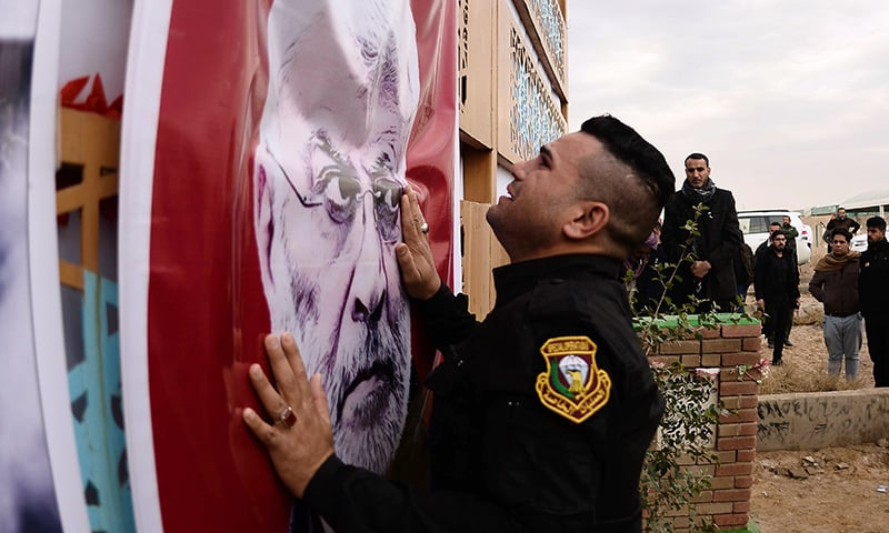 A member of Iraq's special forces sheds tears in front of a portrait of the slain chief of the Hashed al-Shaabi paramilitary network, Abu Mahdi al-Muhandis, ahead of his burial in the central Iraqi shrine city of Najaf on Wednesday. — AFP