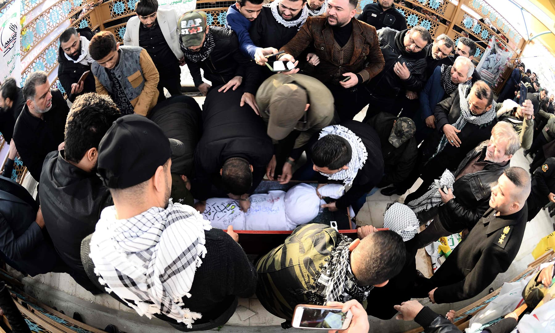 "Iraqi mourners, including members of Hashed al-Shaabi paramilitary network, gather around the coffin of the group's slain chief Abu Mahdi al-Muhandis ahead of his burial in the Wadi al-Salam (""Valley of Peace""), in Iraq's holy city of Najaf on Wednesday. — AFP"
