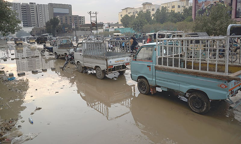 OVERFLOWING sewage on M.A. Jinnah Road on Wednesday creates problems in the smooth flow of traffic.—Shakil Adil/White Star