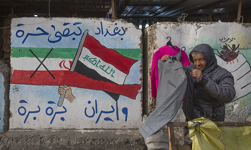 "A street vendor displays clothes next to graffiti with Arabic that reads, ""Baghdad is free and Iran out,"" in Tahrir Square, Baghdad, Iraq, on Wednesday. — AP"