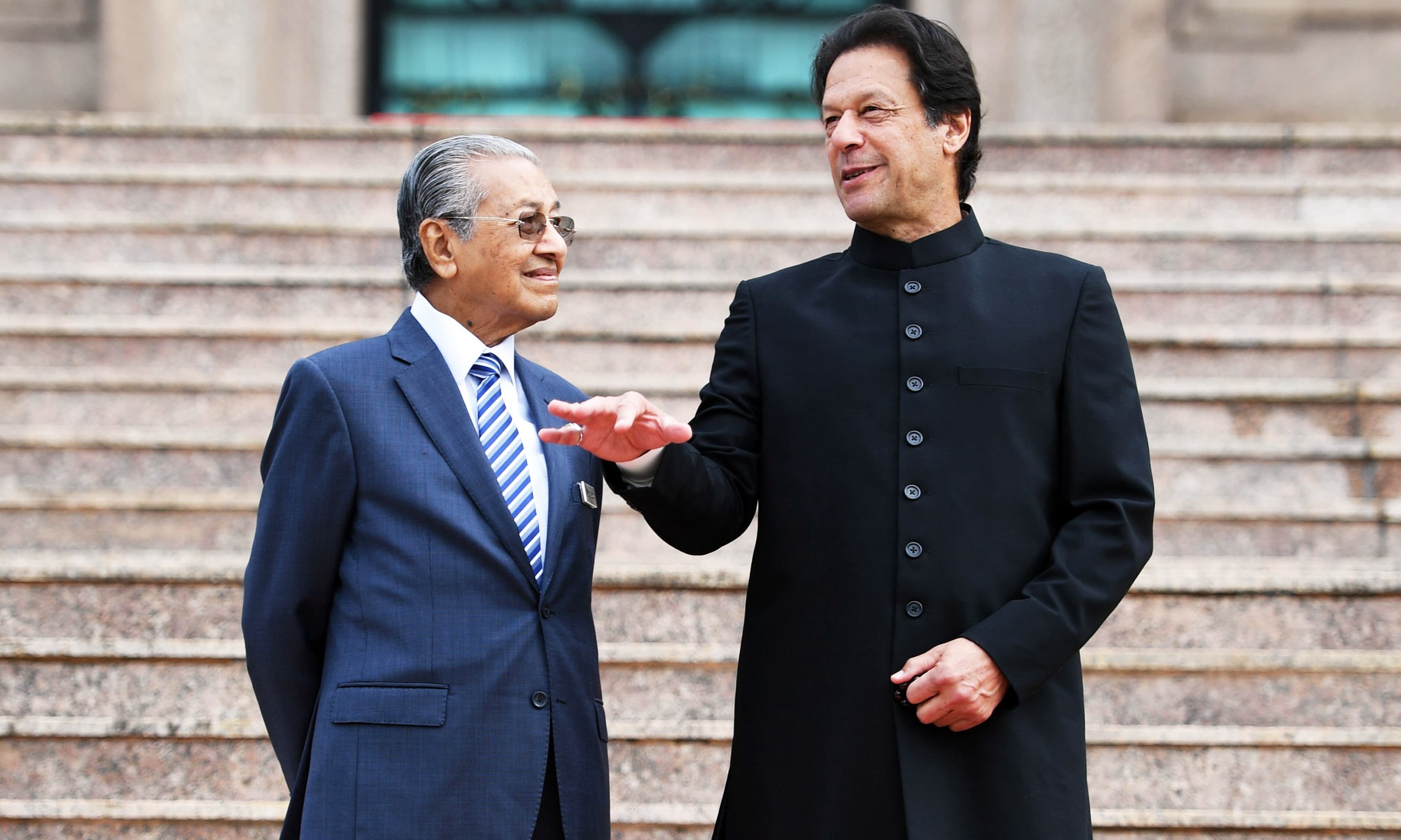 Malaysia's PM Mahathir Mohamad listens to PM Imran Khan during a welcoming ceremony at the prime minister's office in Putrajaya in November 2018. — AFP
