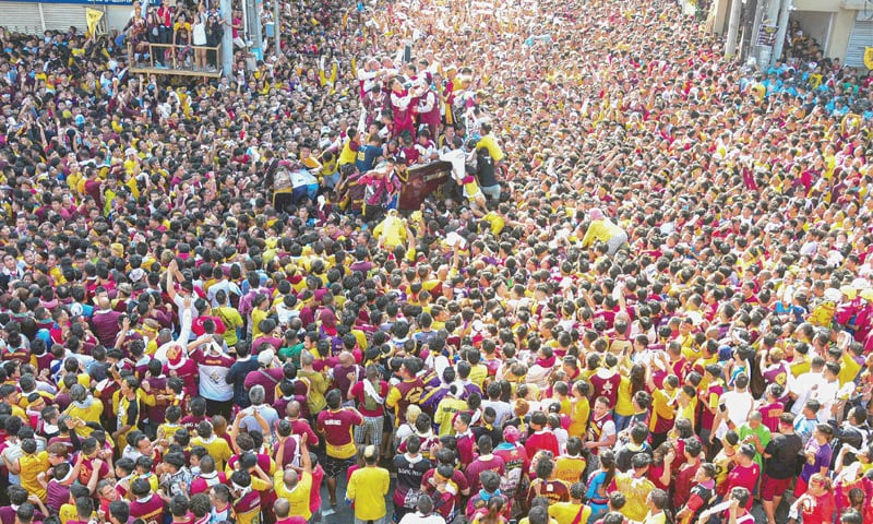 MANILA: Devotees follow a carriage transporting the statue of the Black Nazarene during an annual religious procession on Thursday.—AFP