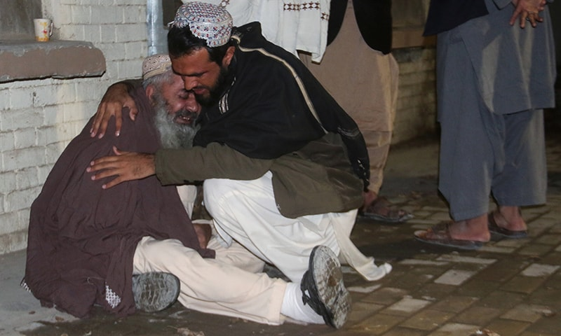 Men comfort each other as they mourn the death of a relative who was killed in a bomb blast in a mosque, at a hospital morgue in Quetta. — Reuters