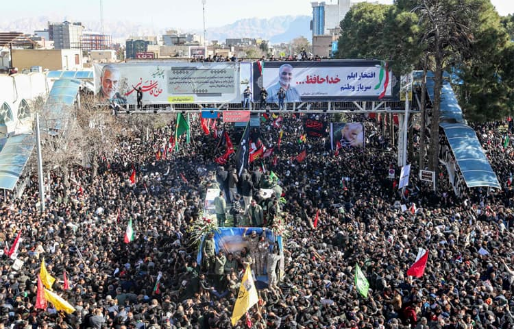 Mourners gather around a vehicle carrying the coffin of slain Gen Qassem Soleimani in his hometown Kerman | AFP