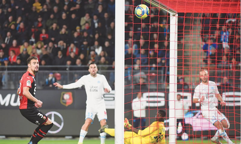 RENNES: Olympique de Marseille's Kevin Strootman (second L) scores past Rennes goalkeeper Edouard Mendy during their Ligue 1 match at the Roazhon Park.—AFP