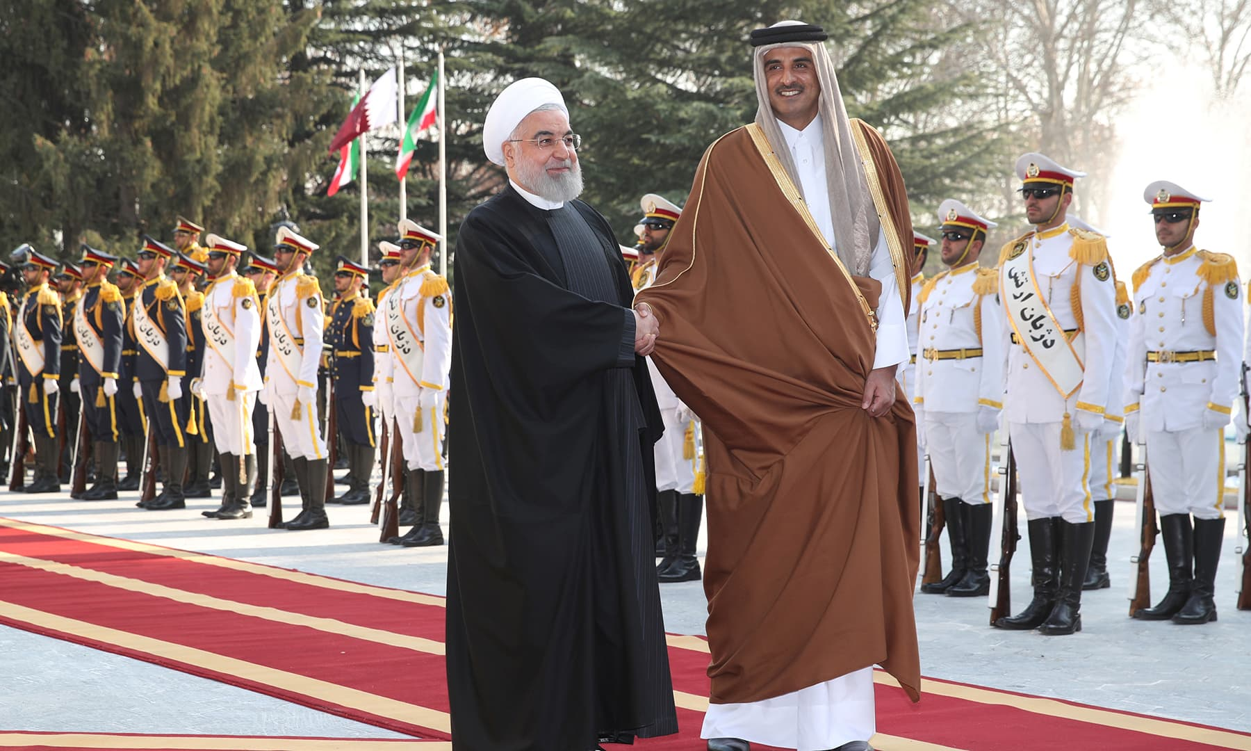 Iranian President Hassan Rouhani shakes hands with Qatar Emir Sheikh Tamim bin Hamad bin Khalifa Al-Thani during a welcome ceremony in Iran on  Jan 12. — Reuters
