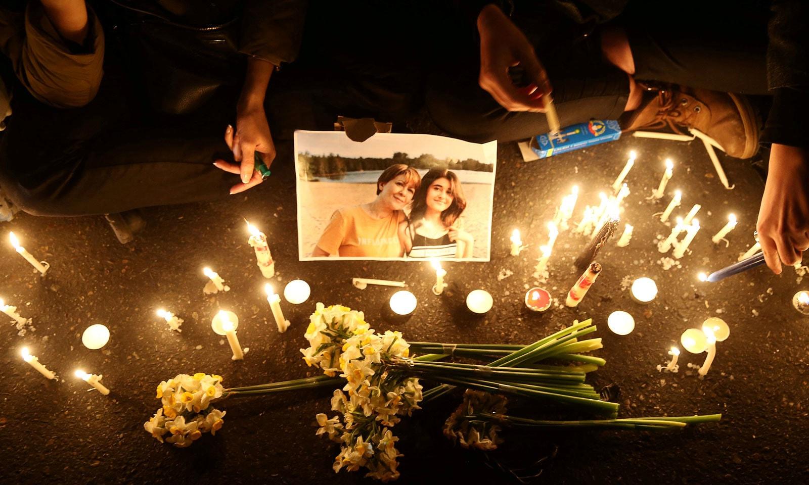 طیارہ حادثے میں ہلاک افراد کو خراج عقیدت پیش کرتے ہوئے شمعیں روشن کی گئیں— فوٹو: رائٹرز