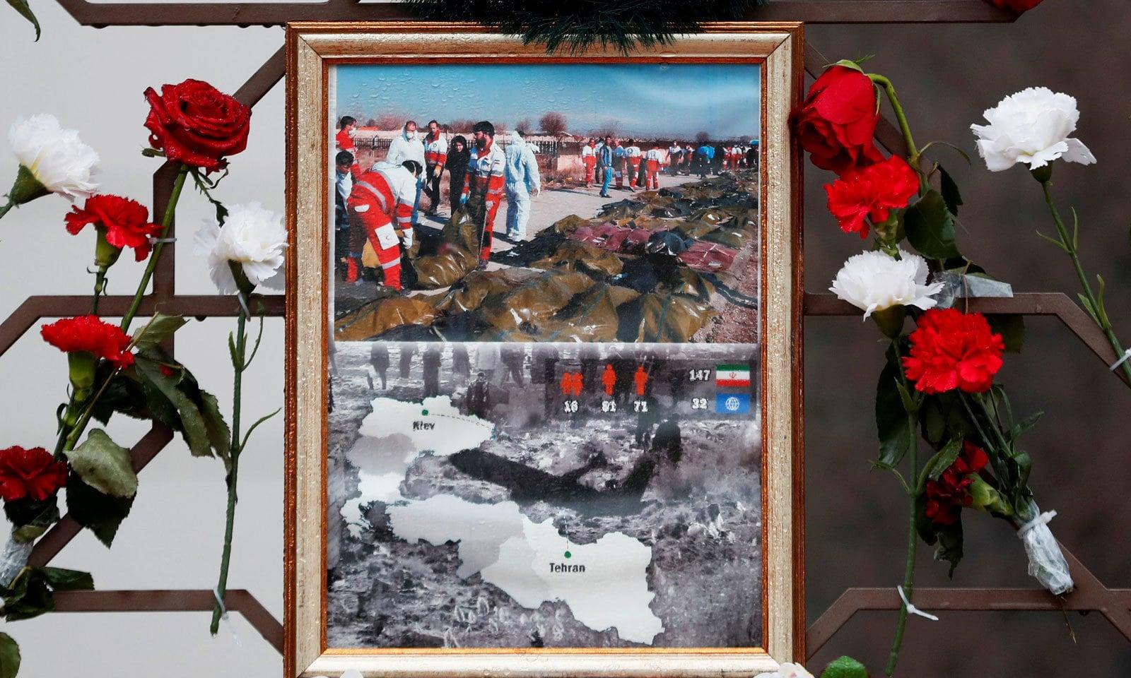 حادثے کی تصاویر کے پاس لوگوں نے متاثرین سے عقیدت کے لیے پھول رکھے ہوئے ہیں— فوٹو: رائٹرز